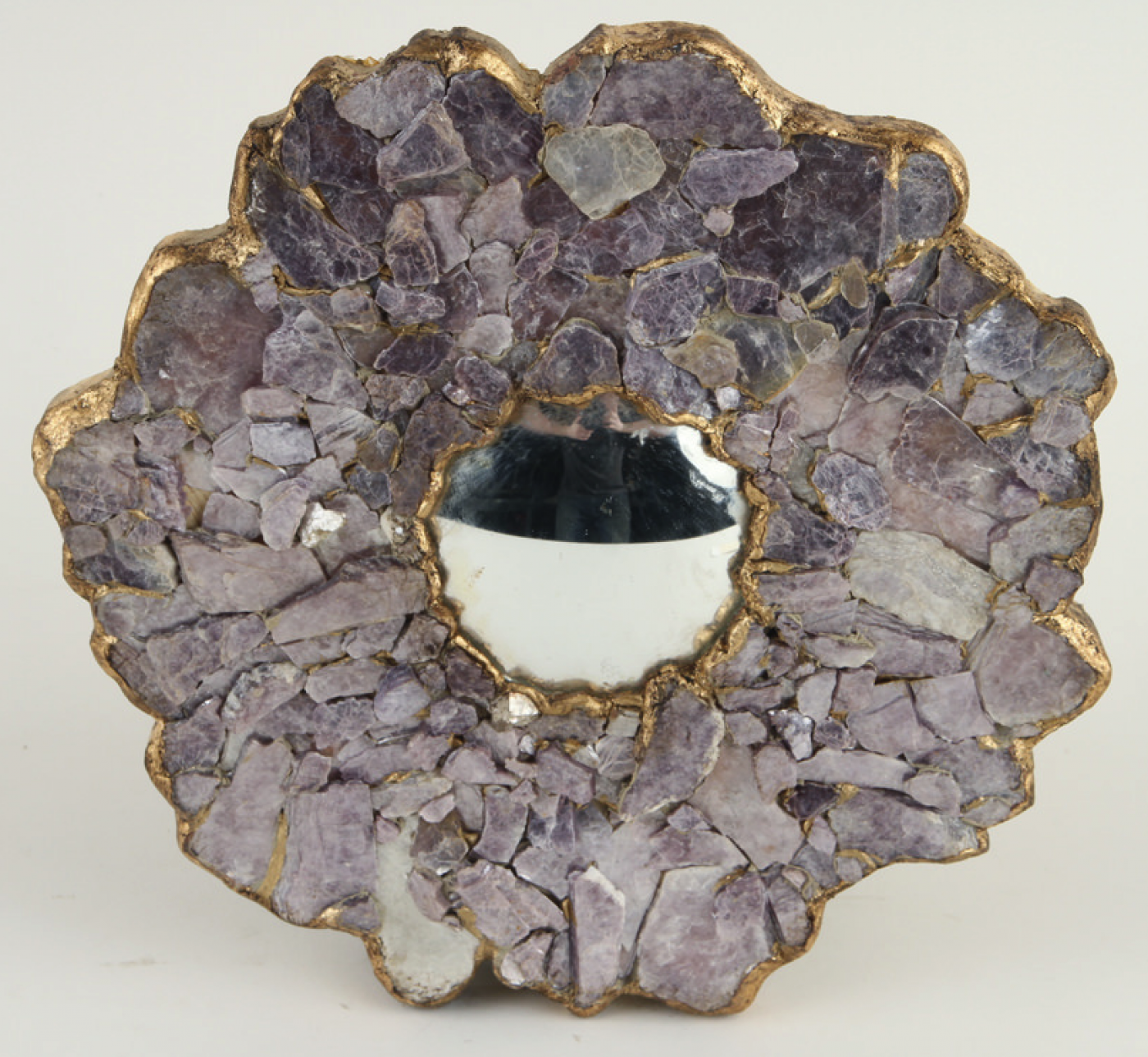 A decorative convex mirror surrounded by faceted stones.