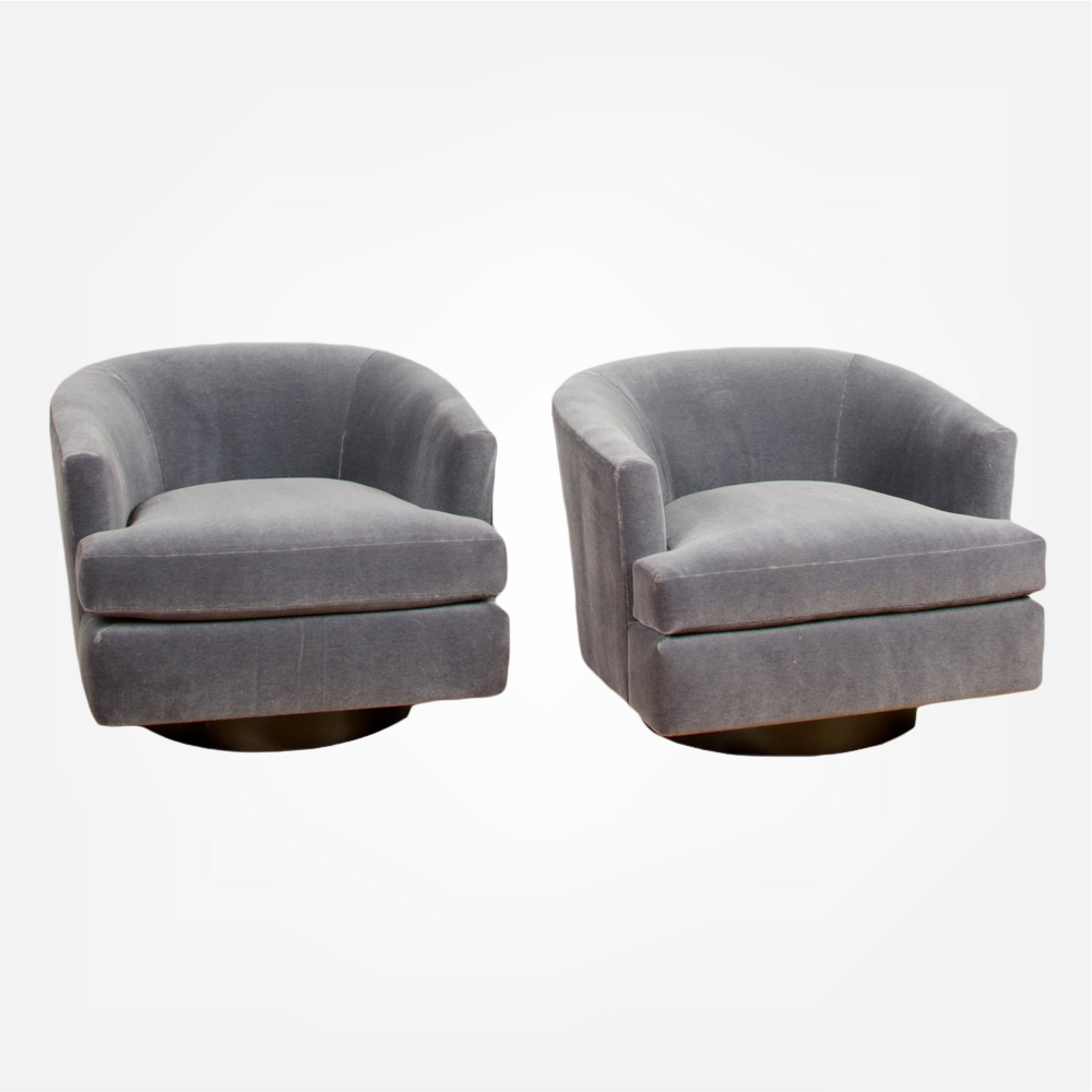 A pair of Mid-Century barrel back swivel chairs in the manner of Milo Baughman. 1970s.